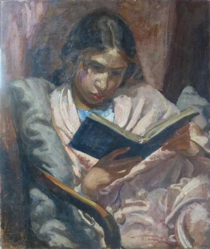 Girl seated reading wrapped in pink blanket