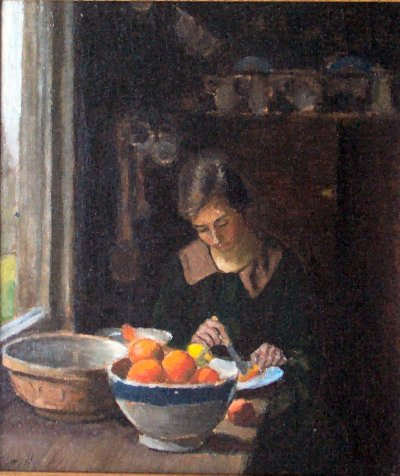 Portrait of a young woman cutting oranges taken from a blue rimmed stoneware bowl
